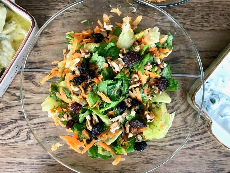 Salada fresca da noz com fatias raspadas da cenoura na bacia de vidro na tabela de jantar fotos de stock royalty free