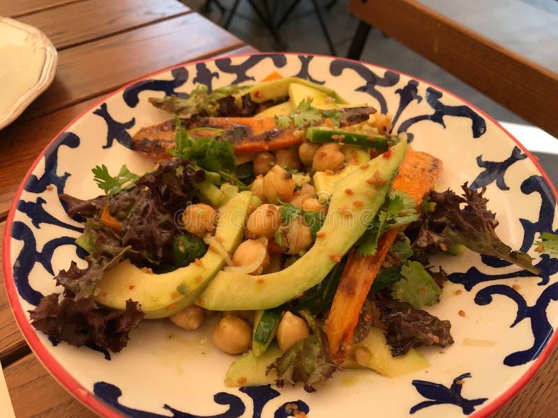 A salada fresca do abacate com grãos-de-bico e fatias da cenoura serviu no restaurante imagem de stock