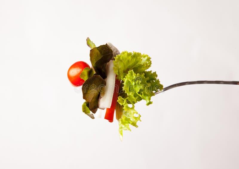 Salada fresca e na forquilha isolada no fundo branco imagens de stock