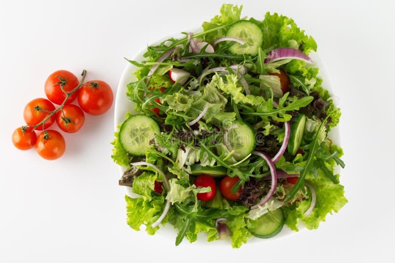 Salada fresca em uma placa isolada no branco fotos de stock royalty free