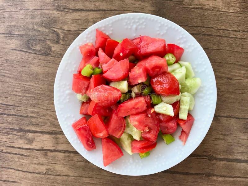 Salada fresca orgânica do tomate com o pepino na placa imagem de stock