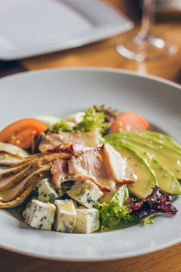 Salada fresca saboroso com os ingredientes diferentes como a salada, tomates, carne, queijo no restaurante na placa branca fotografia de stock royalty free