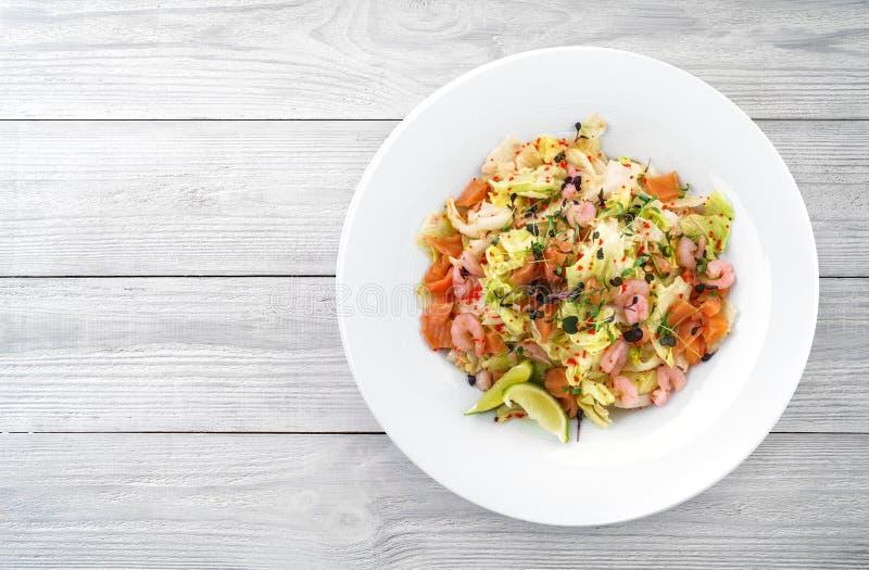 Salada fresca saudável com alface, verdes, caviar vermelho, camarão, salmão da faixa na placa no fundo de madeira claro Alimento  fotografia de stock