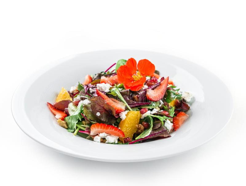 Salada fresca saudável com verdes da mistura, morango, laranja, porcas, queijo creme e as flores comestíveis na placa no branco i foto de stock royalty free