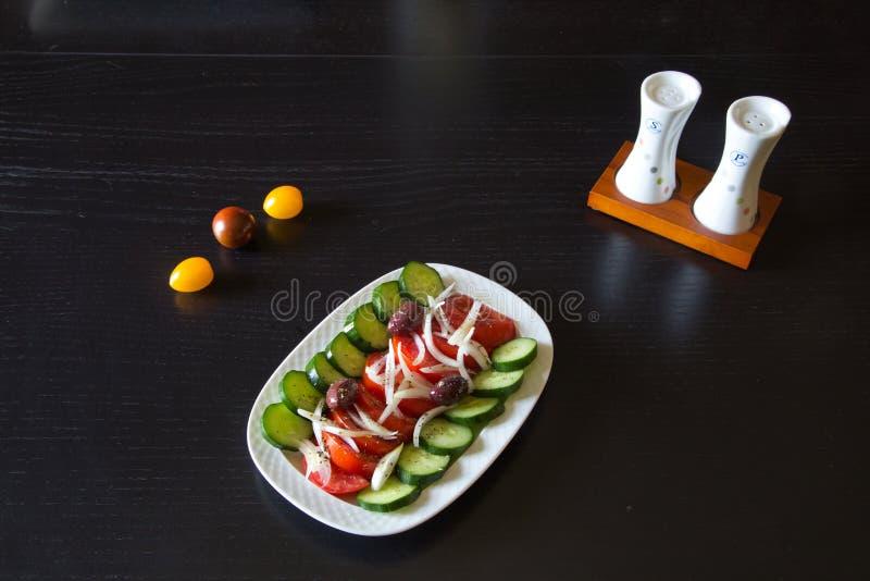Salada grega com azeitonas pretas orgânicas, os tomates suculentos, pimenta vermelha, cebola e pepino foto de stock royalty free