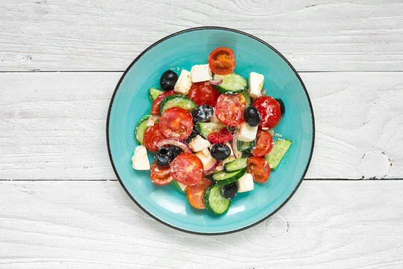 Salada grega com legumes frescos, queijo de feta e azeitonas pretas em uma placa na tabela de madeira branca fotografia de stock royalty free