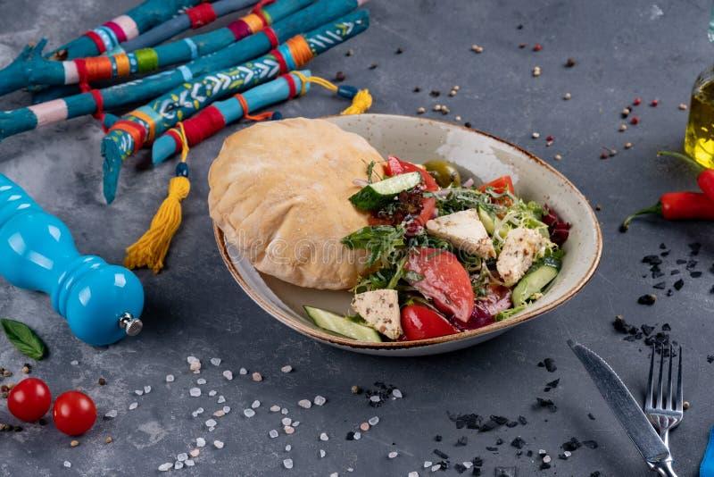 Salada grega com os tomates de cereja frescos, o queijo de feta, azeitonas pretas, manjericão e cebola no fundo de pedra preto, p imagem de stock royalty free