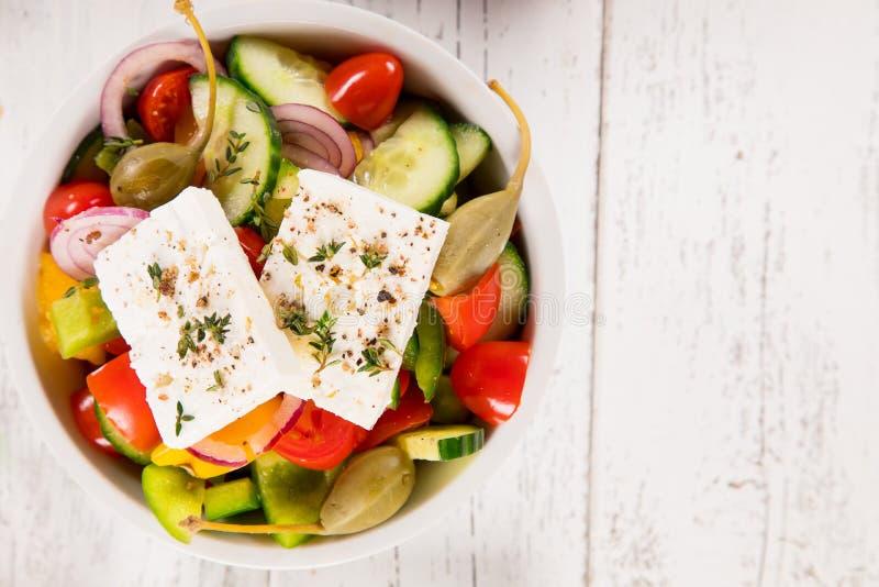 Salada grega com queijo de feta, os legumes frescos e as azeitonas no fundo de madeira branco velho fotografia de stock royalty free