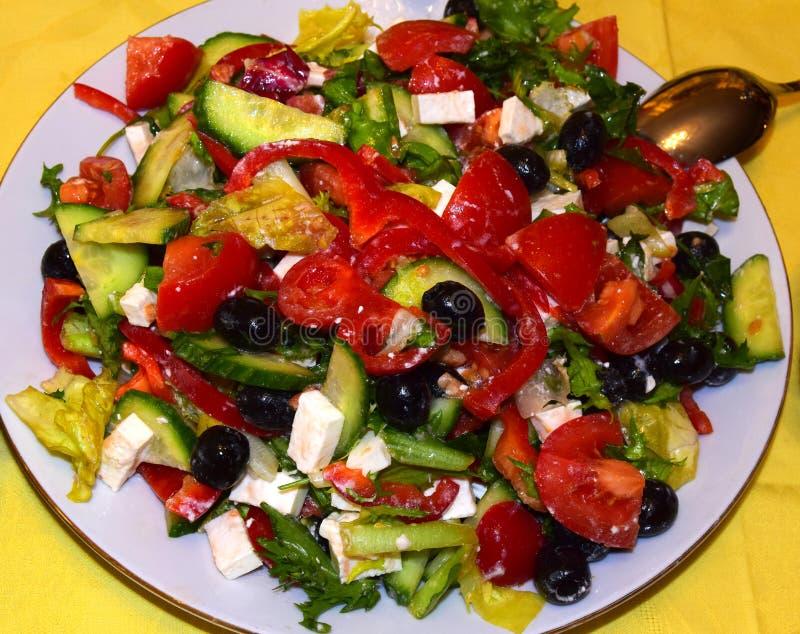 A salada grega consiste em tomates, em pepinos, em azeitonas, na pimenta doce vermelha, no queijo de feta e no azeite fotos de stock