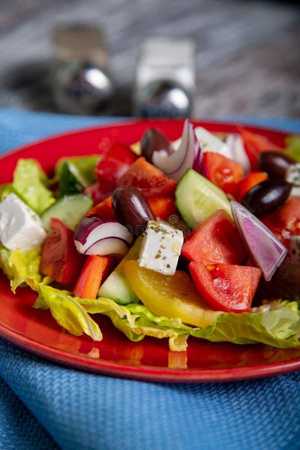 Salada grega do pepino fresco, do tomate, da pimenta doce, da alface, da cebola vermelha, do queijo de feta e das azeitonas com a fotos de stock royalty free