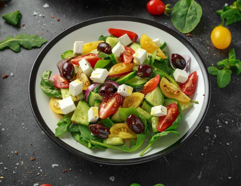 Salada grega fresca com pepino, tomate de cereja, alface, a cebola vermelha, o queijo de feta e azeitonas pretas Alimento saudáve foto de stock royalty free