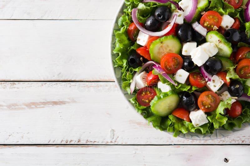 Salada grega fresca na bacia com azeitona preta, tomate, queijo de feta, pepino e cebola na tabela de madeira branca imagem de stock