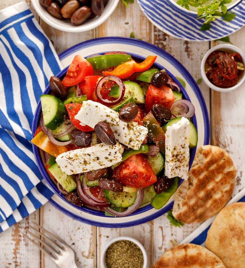 Salada grega Salada grega tradicional que consiste em legumes frescos tais como tomates, pepinos, pimentas, cebolas, oréganos e o foto de stock