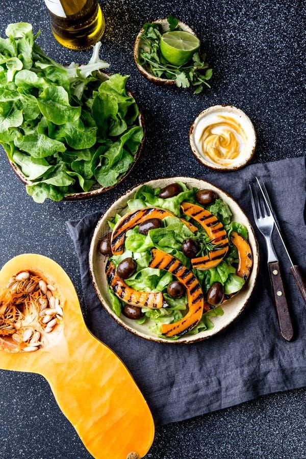 Salada grelhada da abóbora e da alface no fundo escuro fotos de stock royalty free