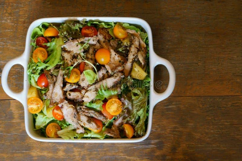 Salada grelhada da carne de porco com alface e tomate na tabela de madeira fotografia de stock