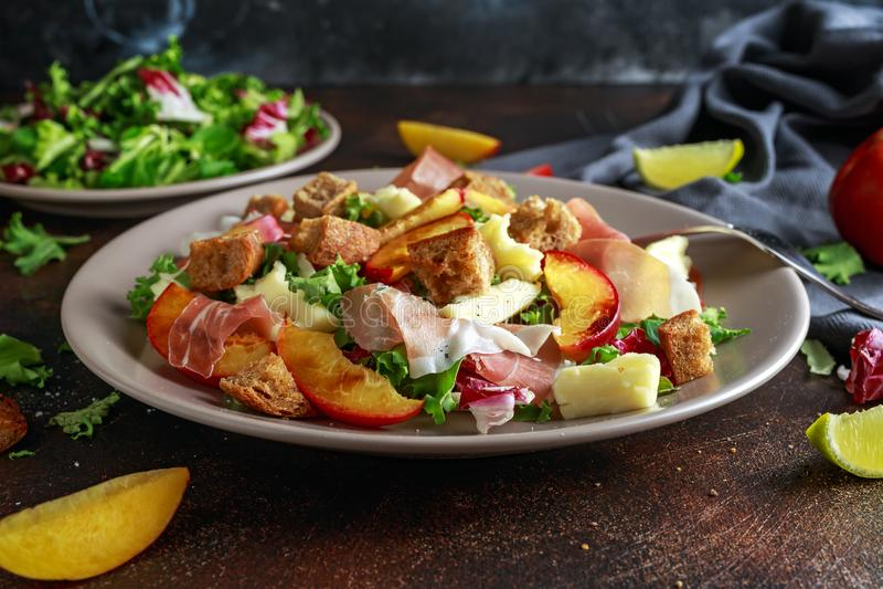 Salada grelhada fresca do pêssego com mistura, queijo, o prosciutto e o pão torrado verdes fotografia de stock
