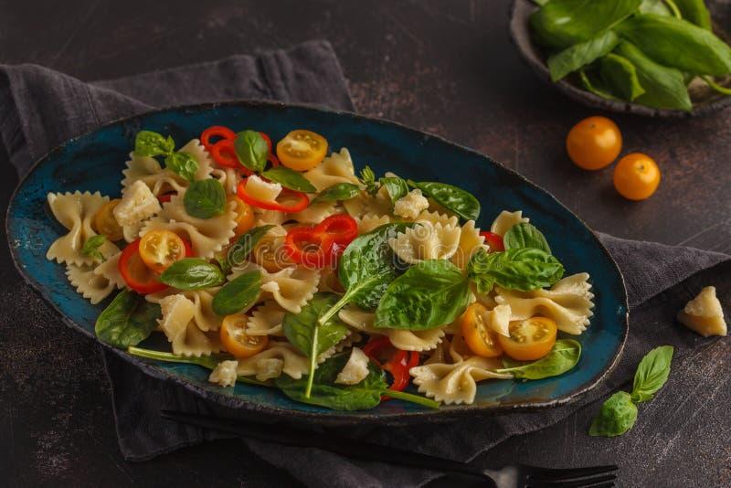 Salada italiana do farfalle da massa com vegetais e espinafres ser fotografia de stock royalty free