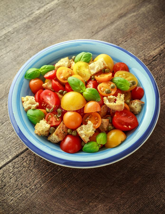 Salada italiana tradicional caseiro de Panzanella, de tomate com os tomates de cereja vermelhos, amarelos, alaranjados, alcaparra foto de stock