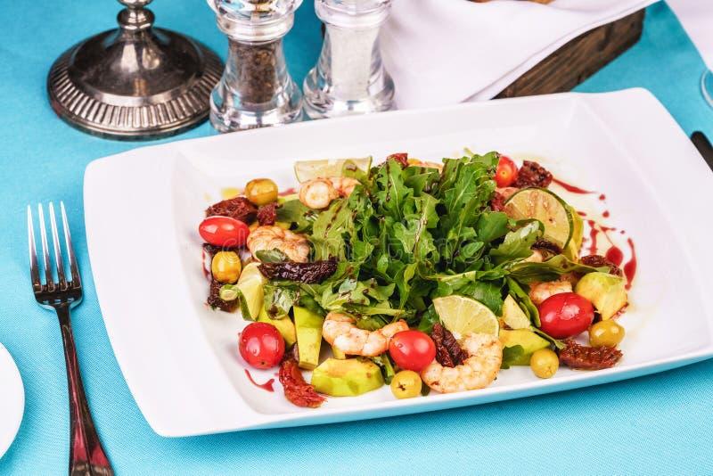 Salada mediterrânica com camarão grelhado, tomate cereja, rúcula, verduras, abacate, cal, azeitonas, molho balsâmico imagem de stock royalty free