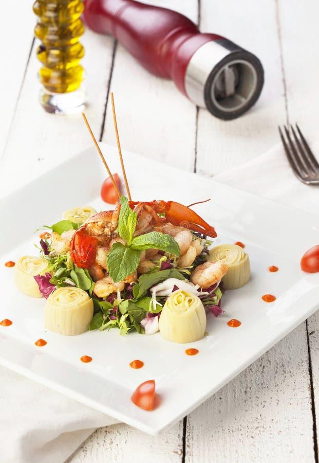 Salada misturada com hortelã e tomate e óleo em um fundo de madeira fotos de stock royalty free