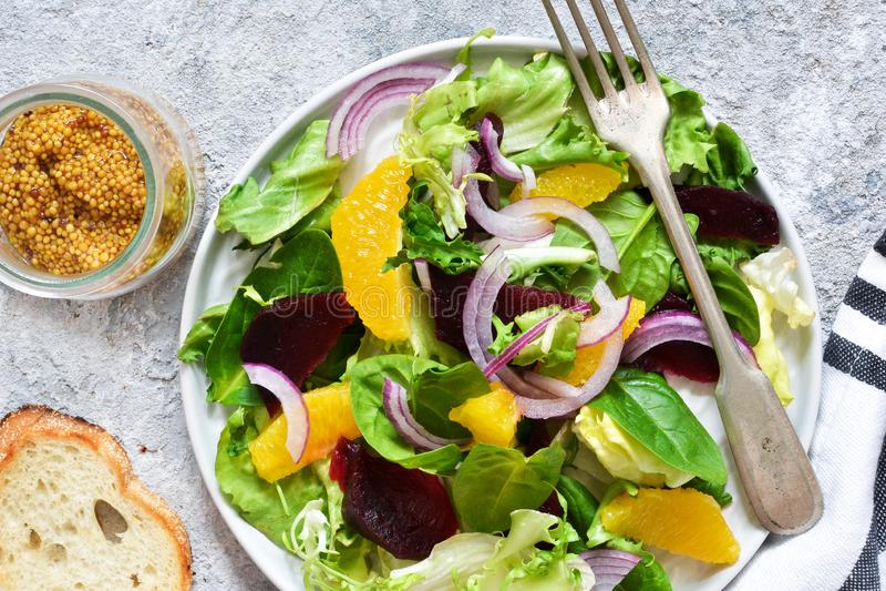 Salada misturada com laranja, beterrabas e molho na mesa de cozinha Alimento biol?gico vegan fotografia de stock