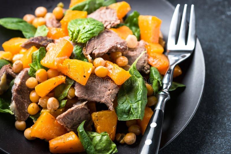 Salada morna com abóbora, carne cozida, espinafres e grãos-de-bico foto de stock