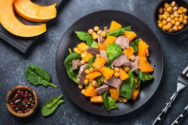 Salada morna com abóbora, carne cozida, espinafres e grãos-de-bico fotos de stock