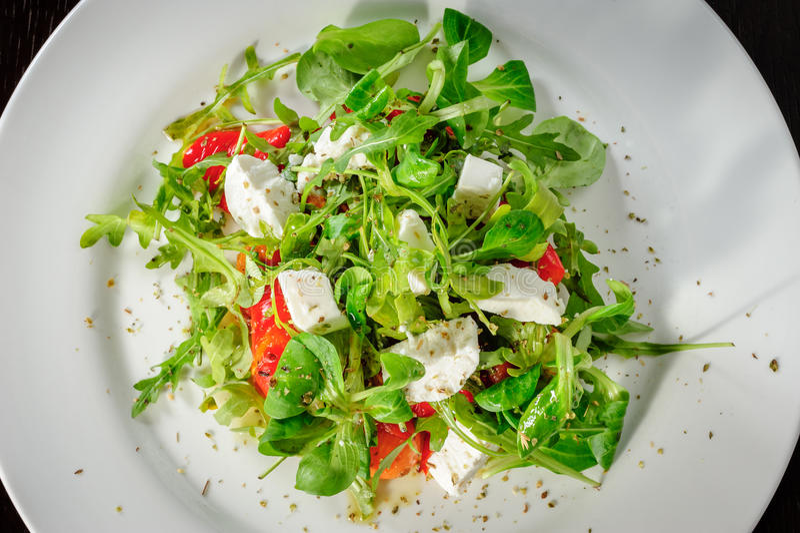 A salada morna com tomates, ruccola, espinafre, cozinhou a pimenta de sino e o queijo imagem de stock