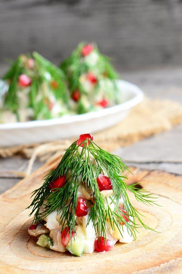 Salada na forma de árvores de Natal em uma placa de madeira Salada caseiro com carne, cogumelos, pepinos e ovos fotografia de stock royalty free