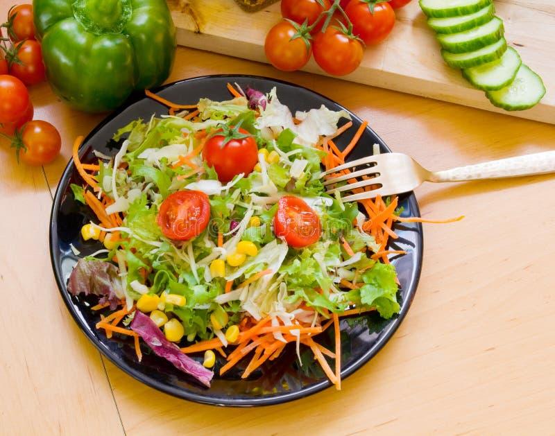 Salada no prato preto fotografia de stock