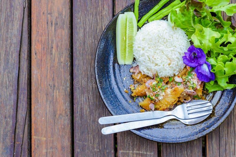 A salada picante dos peixes, flores da ervilha, alface, pepino está no prato O alimento está na tabela de madeira foto de stock