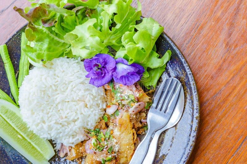 A salada picante dos peixes, flores da ervilha, alface, pepino está no prato O alimento está na tabela de madeira imagem de stock