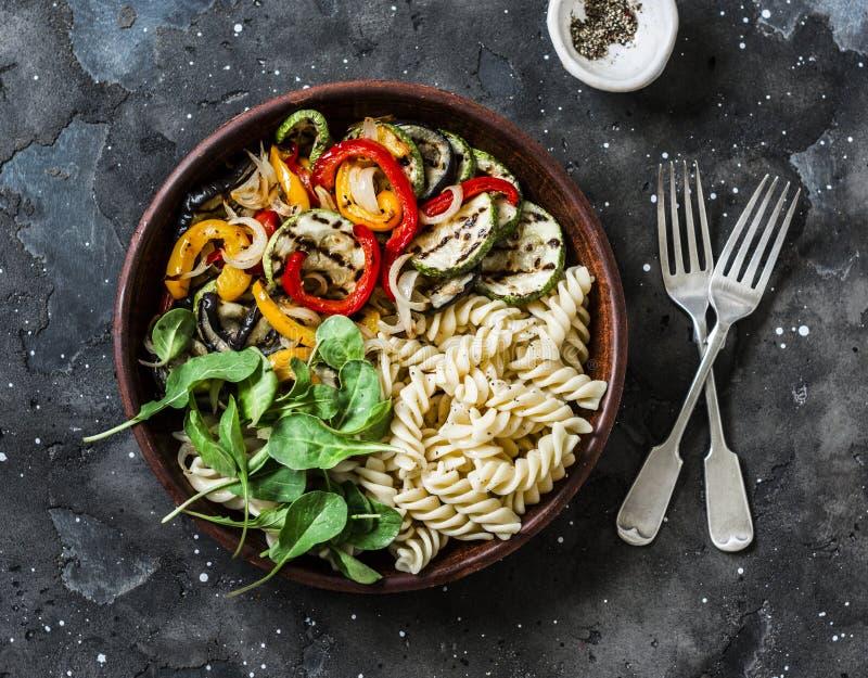 Salada Roasted dos vegetais e dos antipasti da massa do fusilli no fundo escuro, vista superior fotos de stock royalty free