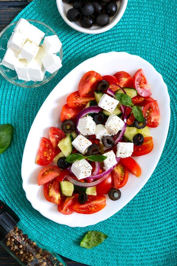 Salada saboroso com legumes frescos, feta da vitamina, azeitonas pretas, molho da manjericão em uma placa branca em um fundo de m fotos de stock