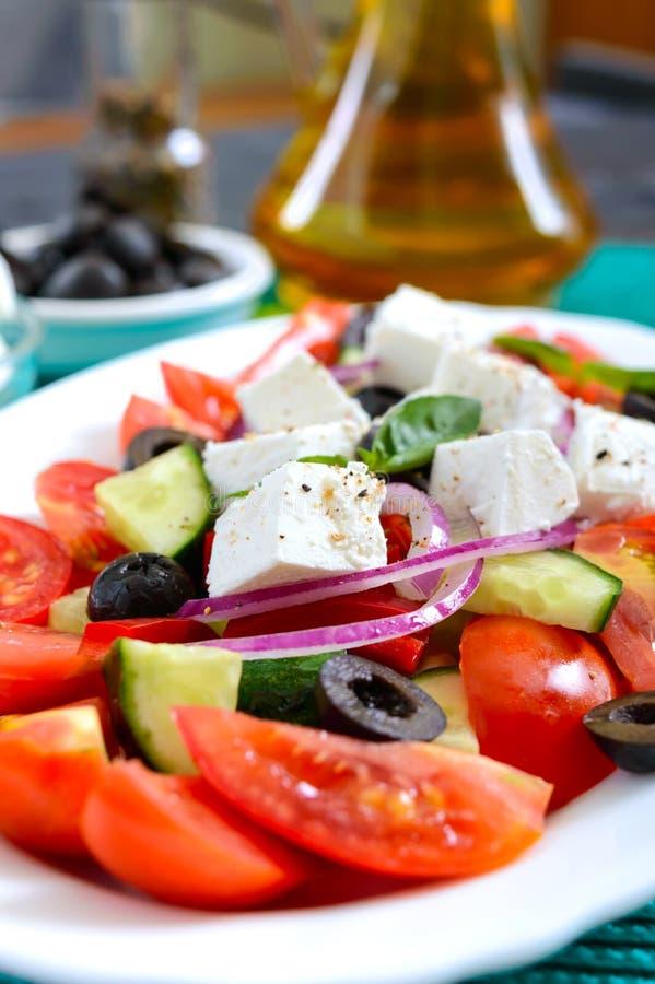 Salada saboroso com legumes frescos, feta da vitamina, azeitonas pretas, molho da manjericão em uma placa branca em um fundo de m fotos de stock royalty free