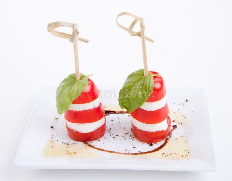 Salada saboroso da mussarela do tomatoe com manjericão no branco foto de stock royalty free