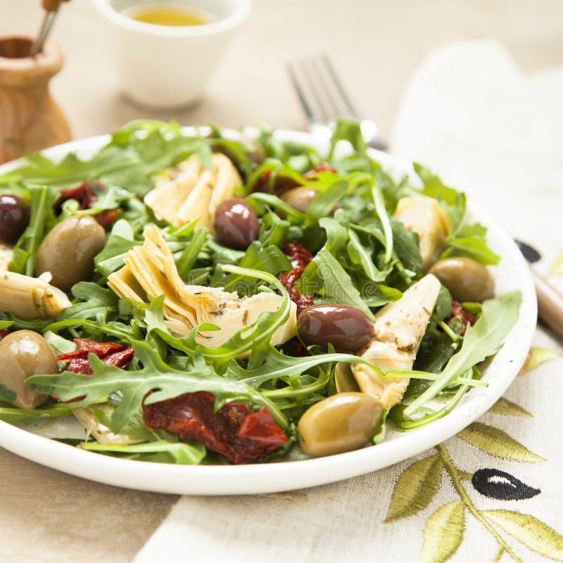 A salada saboroso do vegetariano com alcachofra, foguete, sol-secou tomates e azeitonas imagem de stock royalty free