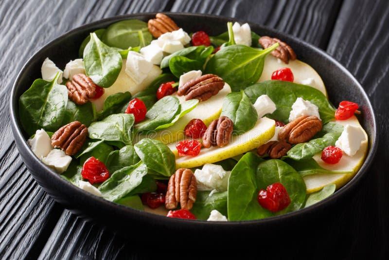 Salada saboroso saudável do alimento feita das peras, dos espinafres do bebê, das nozes-pecã, do queijo de feta e do close up das fotografia de stock royalty free