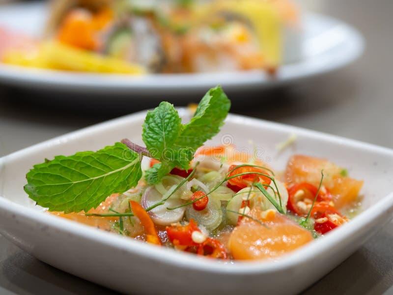 Salada Salmon picante com as ervas tailandesas no molho especial em uma placa branca Salmões cobertos com coentro No restaurante  foto de stock