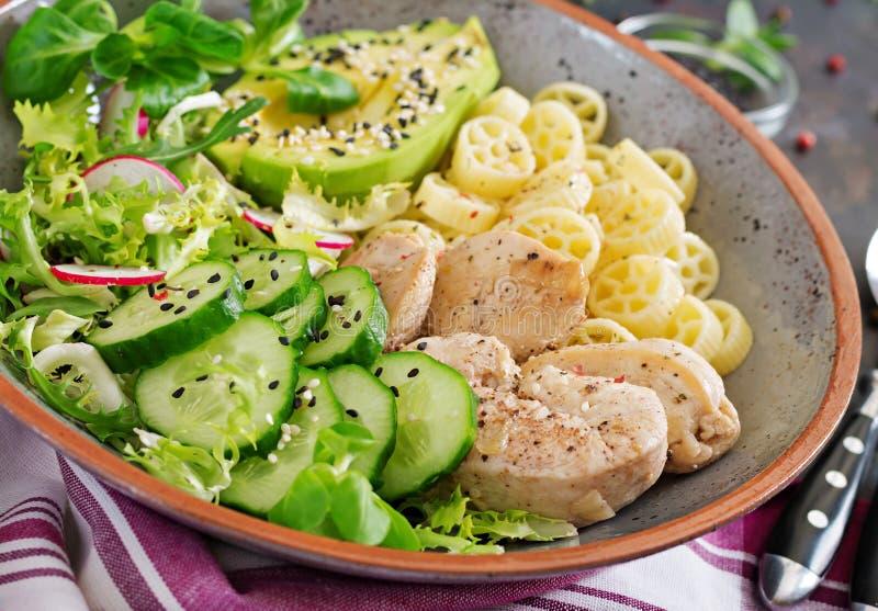 Salada saudável com galinha, abacate, pepino, alface, rabanete e massa no fundo escuro Nutrição apropriada Menu dietético imagem de stock