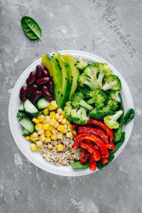 Salada saudável da bacia de buddha com vegetais grelhados Quinoa, espinafres, abacate, feijões, milho doce, brócolis, pepinos e p foto de stock royalty free