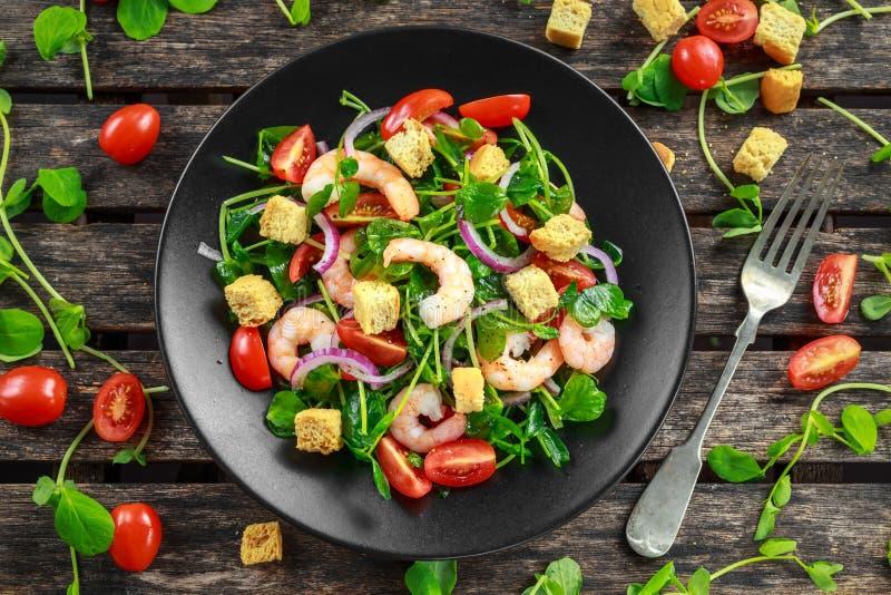 Salada saudável fresca com tomates, cebola vermelha dos camarões na placa preta Alimento saudável do conceito