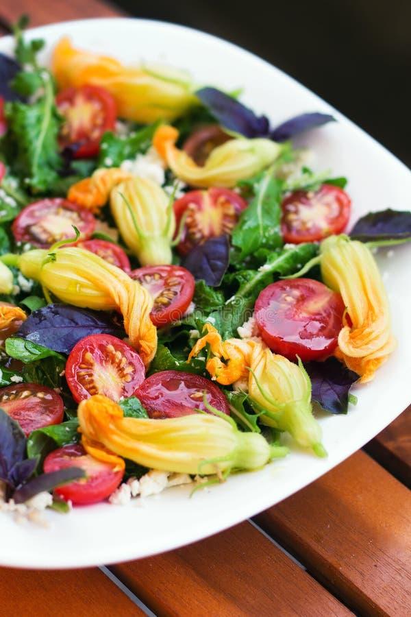 A salada sazonal com rúcula, tomates de cereja, manjericão e abobrinha floresce fotografia de stock