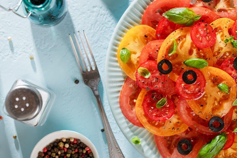 Salada sazonal do tomate com manjericão, azeitonas, especiarias e óleo na tabela azul com forquilha e sal imagens de stock royalty free