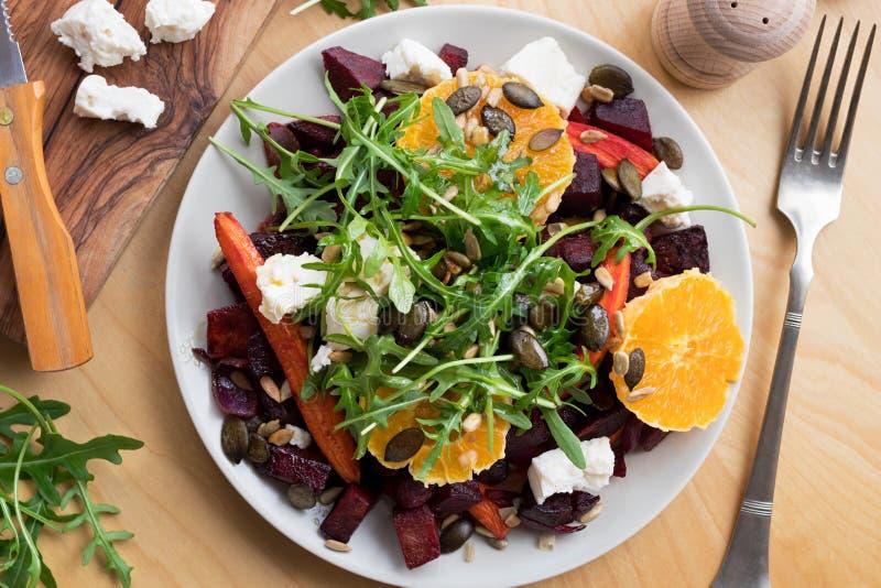Salada vegetal - beterrabas e cenouras cozidas, laranjas, rúcula, goa foto de stock