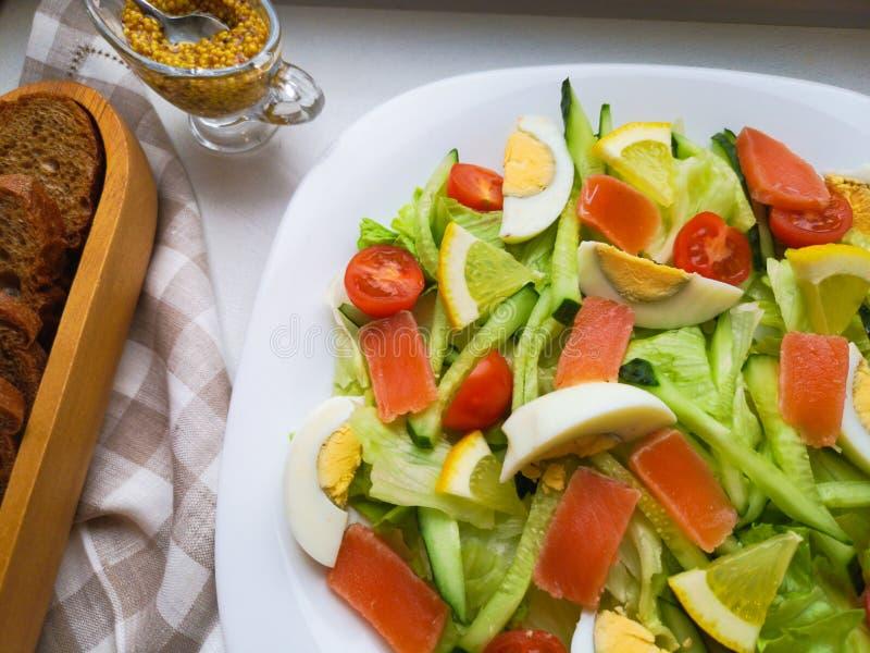 Salada vegetal com Breadon uma placa branca, com pão em uma placa profunda alimento saudável, café da manhã verde fotografia de stock