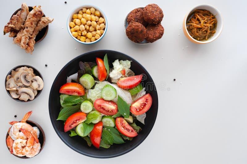 Salada vegetal com os pratos extra na tabela branca foto de stock royalty free