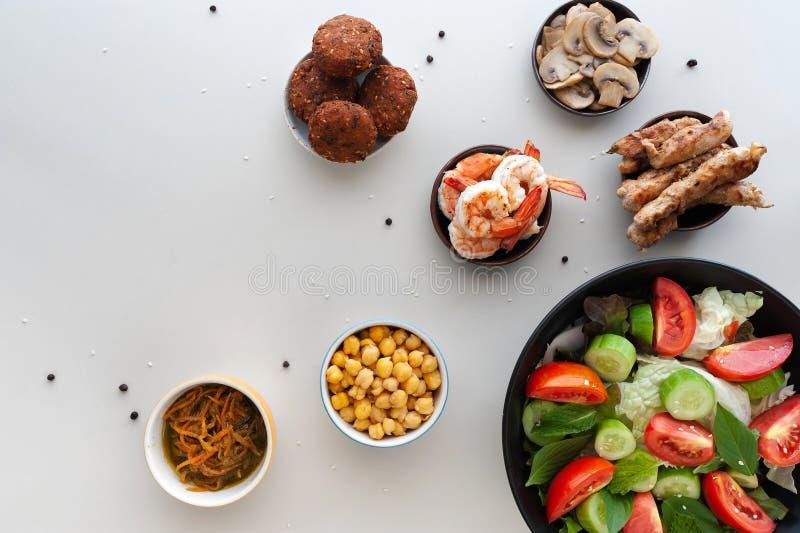 Salada vegetal com os pratos extra na tabela branca imagens de stock