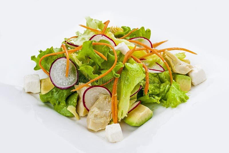 Salada vegetal com rabanete e abacate em uma placa branca imagens de stock