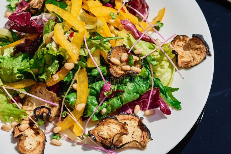 Salada vegetal com verdes frescos e vegetais grelhados em uma tabela escura de vidro no terraço do verão fotografia de stock